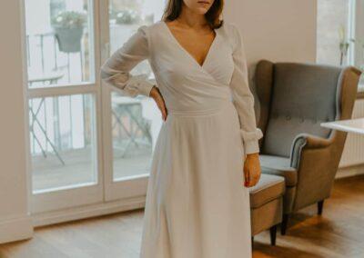 Kopertowa suknia ślubna z długim pufiastym rękawem.